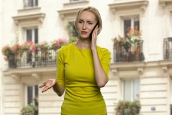 Successful blonde woman is talking on the phone. Serious lady in yellow tunic is having a business call. Beautiful house on the background.