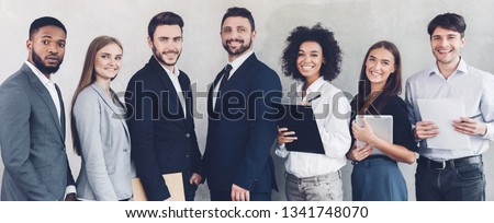 Successful business colleagues looking at camera, having break in office, grey background #1341748070