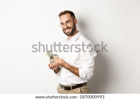 Successful business man counting money and smiling, standing against white background and looking satisfied Foto stock ©