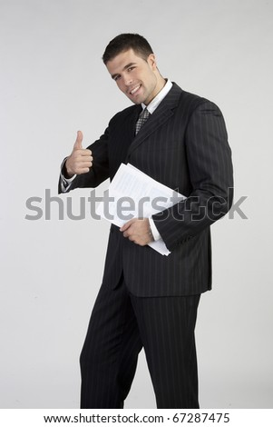 Successful business man gesturing a thumbs up sign on white