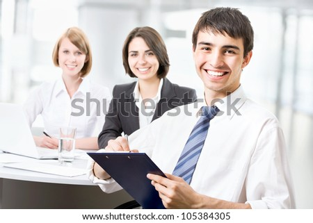 Successful business man sitting with his team at office