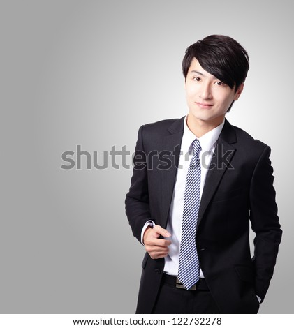 Successful business man smiling and looking friendly with gray background, model is a asian male