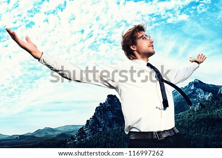 Successful business man standing on a peak of the mountain and purposefully looking away. - stock photo