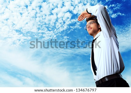 Successful business man standing over blue sky and purposefully looking away.