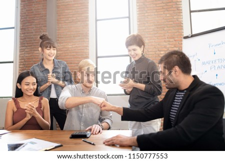Successful business partner giving fist bump after complete a deal on meeting room background. Successful Teamwork Partnership at office. #1150777553