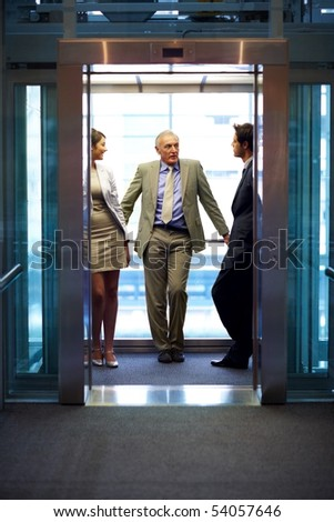 Successful business people standing in office elevator and talking with each other - stock photo