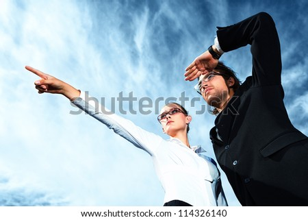 Successful business people  standing over blue sky and purposefully looking away.