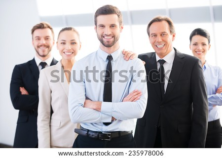 Successful business team. Group of confident business people in formal wear standing close to each other and smiling