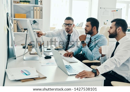 Successful business team. Group of young modern men in formalwear working using computers while sitting in the office