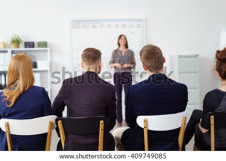 Successful business team in a meeting sitting in a row with their backs to the camera listening to their female team leader give a presentation #409749085