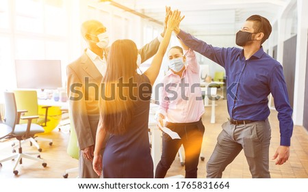 Successful business team with face mask due to corona virus at high five in the office