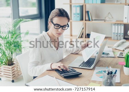 Successful business woman economist in formal wear, sitting at her work place in a light modern design office, making report, in front of laptop, so stylish, concentrated and thoughtful