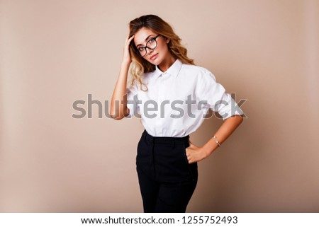 Successful business woman in stylish eyeglasses standing over beige background. White blouse, casual outfit, perfect skin.