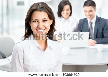 Successful business woman sitting with her team at office - stock photo