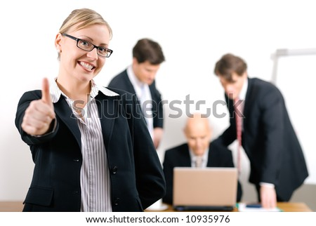 Successful business woman standing in front of her colleagues; selective focus on woman