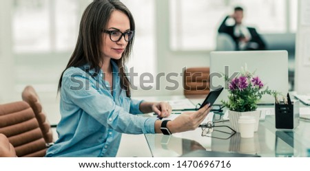 successful business woman with a smartphone in the workplace in the workplace in a modern office #1470696716