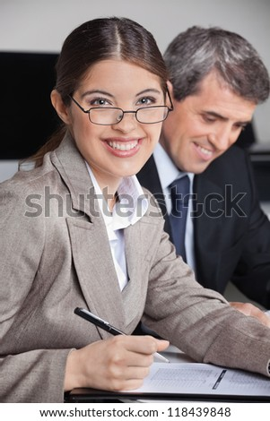 Successful business woman with glasses in the office looking into the camera - stock photo