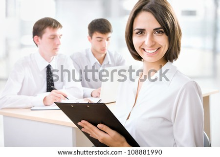 Successful business woman with her staff in background at office -