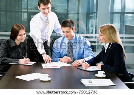 Successful businessman and his colleagues working at office