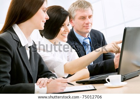 Successful businessman and his pretty colleagues working at office