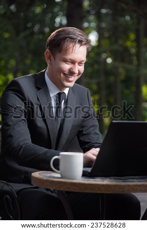 Successful businessman. Attractive young caucasian man in formal wear working on laptop and smiling while sitting at the table outdoors.