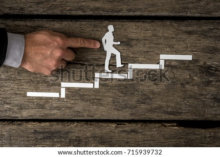 Successful businessman climbing the corporate ladder in a conceptual image using white paper cutouts with the finger of a human male professional aiding his success #715939732