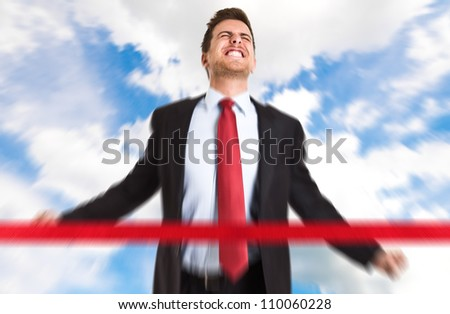 Successful businessman crossing the line - stock photo