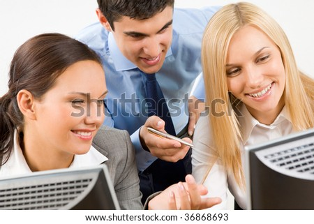 stock photo : Successful businessman explaining something to his pretty colleagues while they looking at monitor