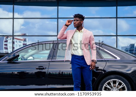 successful businessman handsome African American dreadlocks man in a stylish suit in pink jacket standing in front of a cool new black car on the street