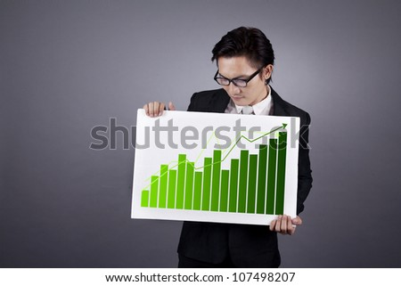 Successful businessman holding green graph of business growth. shot in studio