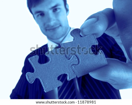 successful businessman in  hand holds red puzzle, close-up - stock photo