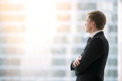 Successful businessman in suit standing in office with hands crossed on chest, looking through window at big city buildings, planning new projects, waiting for meeting to start. Copy space for text