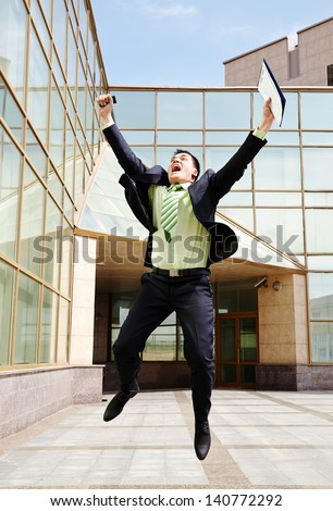 Successful businessman jumping near his office
