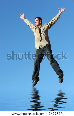 Successful businessman jumping on red rocks