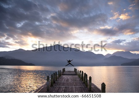 Successful businessman jumping on the pier and watching sunrise and mountain
