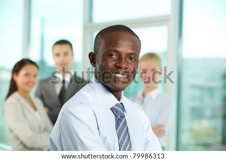 Successful businessman looking at camera with his colleagues on background