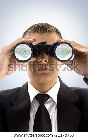 successful businessman looking at currency text with binoculars