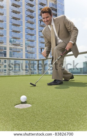 Successful businessman  or man in a suit playing golf on a corporate putting green on roof of a skyscraper office building