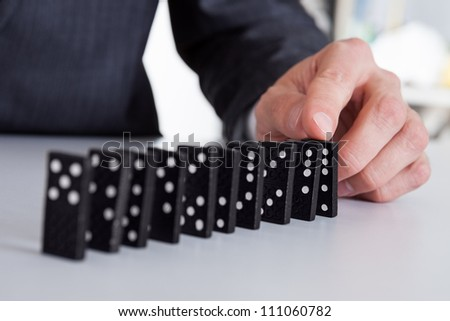 Successful businessman playing domino at the office