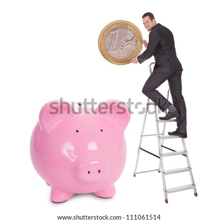Successful businessman putting one euro coin into piggybank. Isolated on white