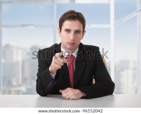 successful businessman seriously sitting at a desk in his office and shows the index finger of the hand