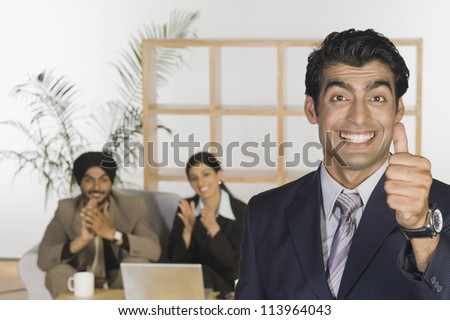 Successful businessman showing thumbs up sign