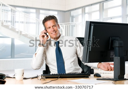 Successful businessman sit at his desk while talking on mobile