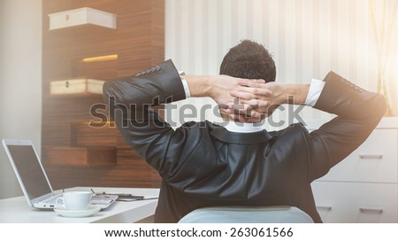 Successful businessman sitting in chair at office.