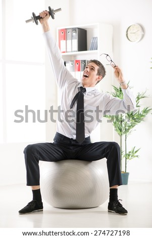 Successful businessman sitting in the office on pilates ball and doing exercise with dumbbells.