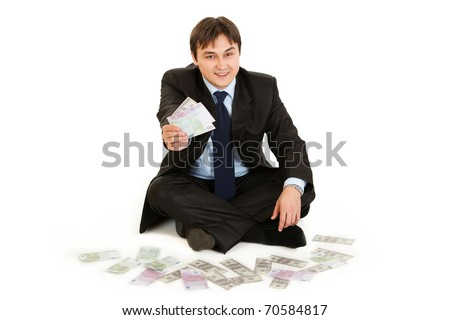 Successful businessman sitting on floor surrounded by money isolated on white - stock photo