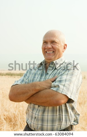 successful businessman standing outdoor on field of wheat