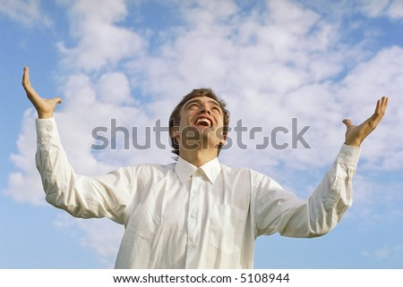 successful businessman with arms outstretched to the sky