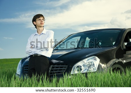 Successful businessman with car on green grassland under blue sky
