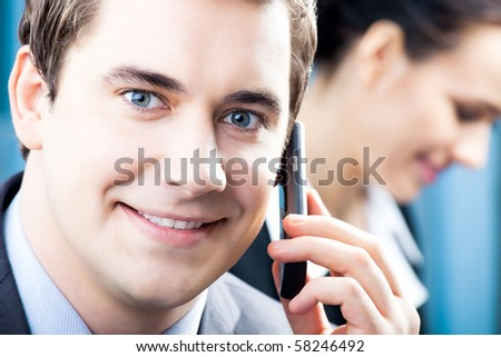 Successful businessman with cellphone and colleague, at office